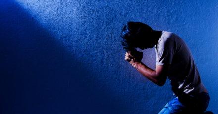 man kneeling down while praying